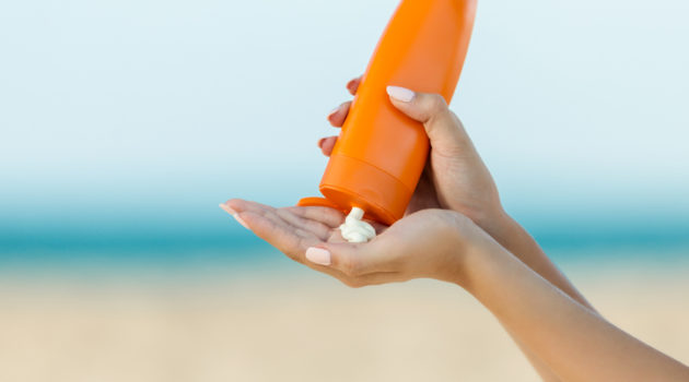 woman pouring sunscreen into hand
