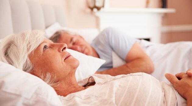 Photo of couple laying in bed.