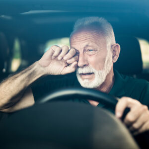 Image of person rubbing their eye while driving